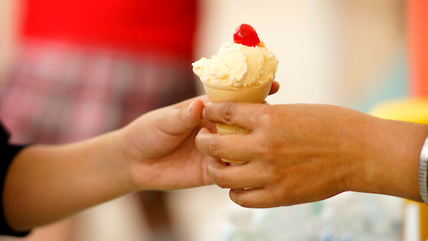 An icecream cone being handed to a child